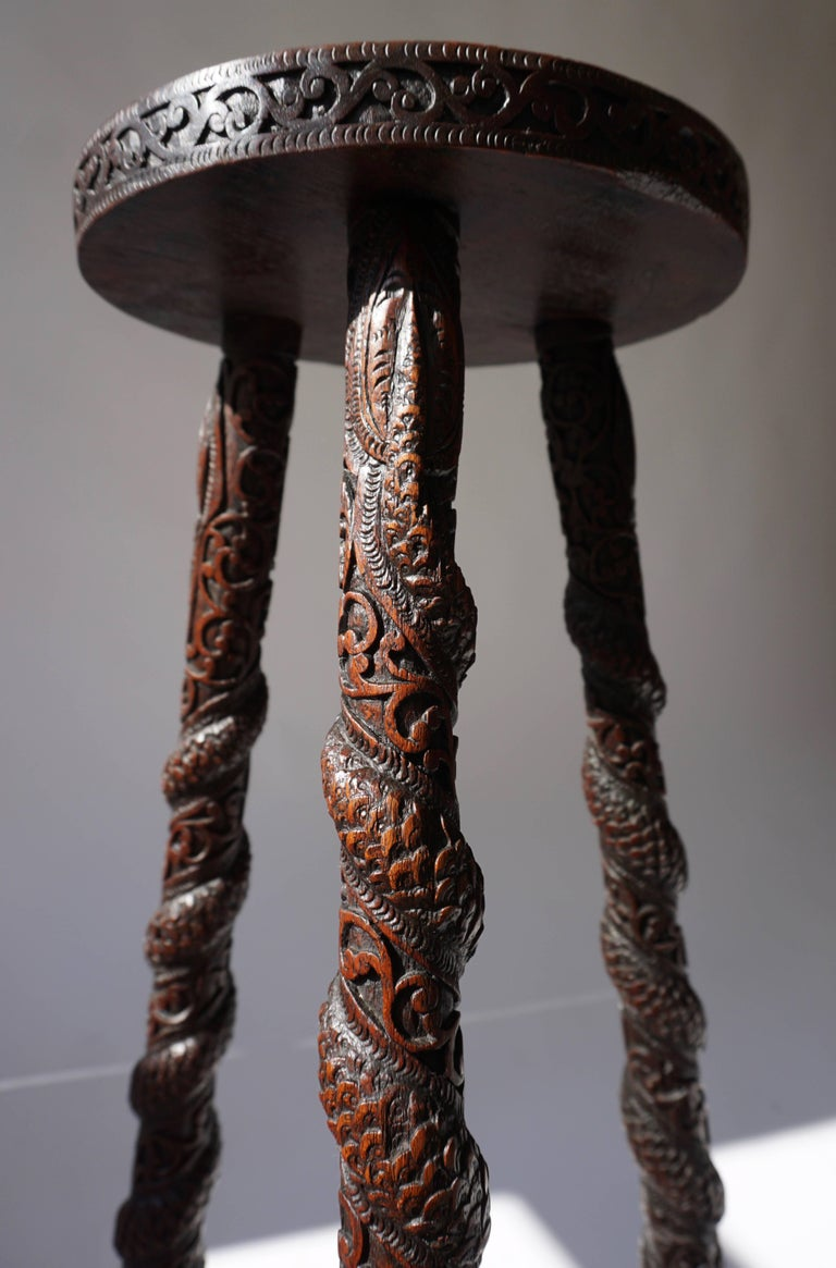 A Burmese hardwood tripod stand, carved all over with scrollwork and flowers, the legs with dragons spiralling down amidst curly branches. The central medallion represents Burmese dancers. 20th century.