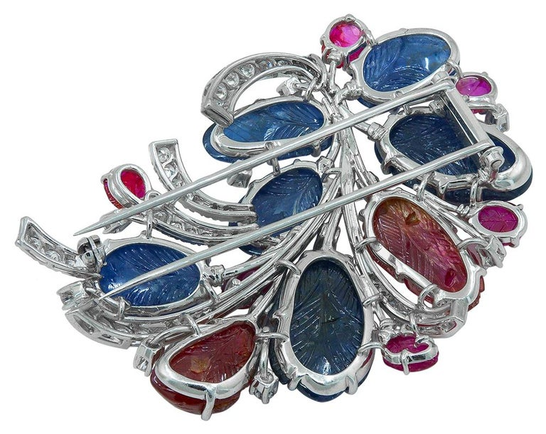 Carved Sapphire Ruby Diamond Flower Brooch in Platinum.  This Carved Sapphire Ruby Diamond Flower Brooch in Platinum captures the moment when nature transitions from winter to spring. Budding petals of hand-sculpted sapphires and rubies emerge from