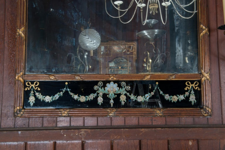 Early 20th century carved wood mirror with striking black background églomisé panels and a basket of flowers. The walnut frame is carved in bundled reed style, with a gentle arch. Old distressed mirror. The small flower below the basket of flowers