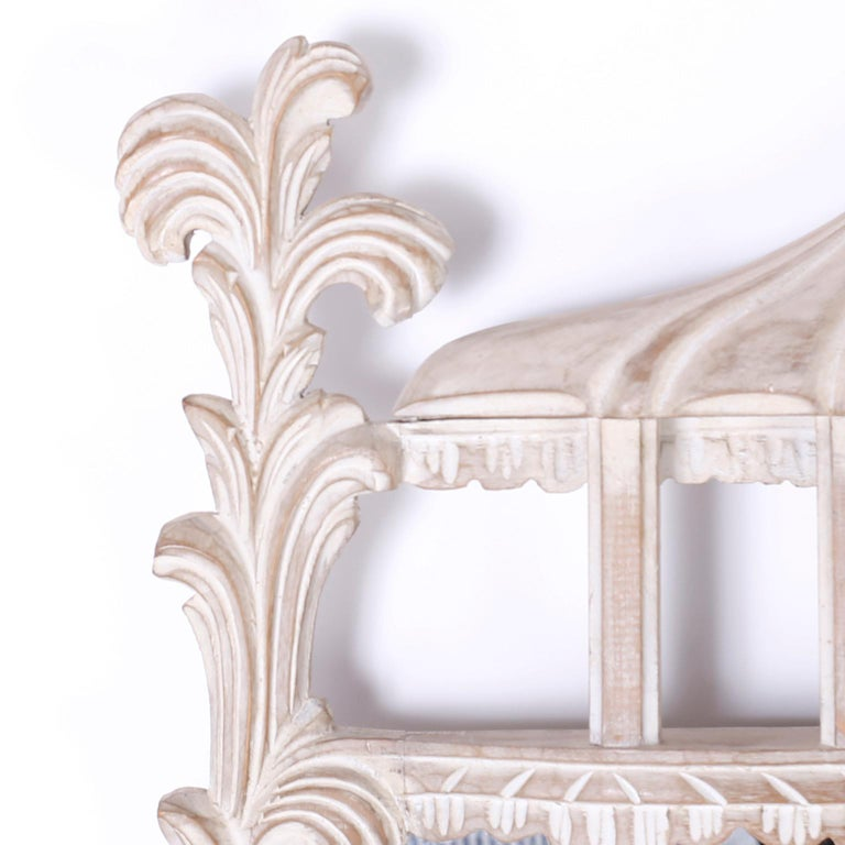 Vintage Italian carved wood wall mirror with a white washed or lime finish over a carved floral frame topped with plumes and a center crest with architectural elements.