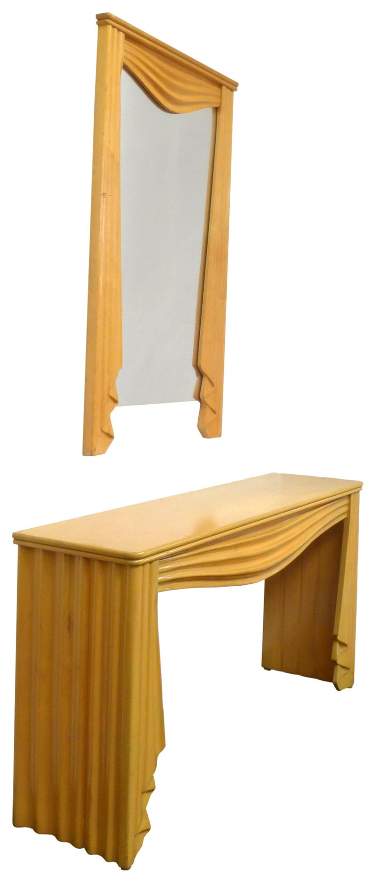 An Italian, carved maple console table and coordinating wall mirror. Very surrealist in feel with the execution of carved wood elements implying draped and undulating fabric. A Trompe-l'œil material effect created by this playful and creative