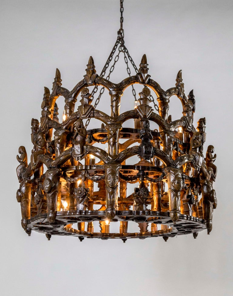 A wooden, oval shaped, folk chandelier from the late 19th century made in Central or South America with Spanish Colonial Gothic influence. The hand carved design is three tiers of arches with lotuses, flowers, praying ladies, faces, and garland. 18