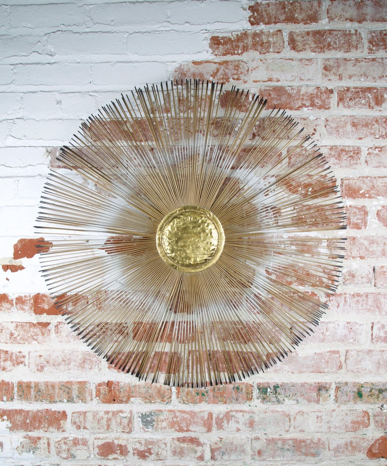 Sunburst wall sculpture with a hammered brass center and two layers of painted rods creating a sunburst effect. The artist hand signed the sculpture on the verso.
