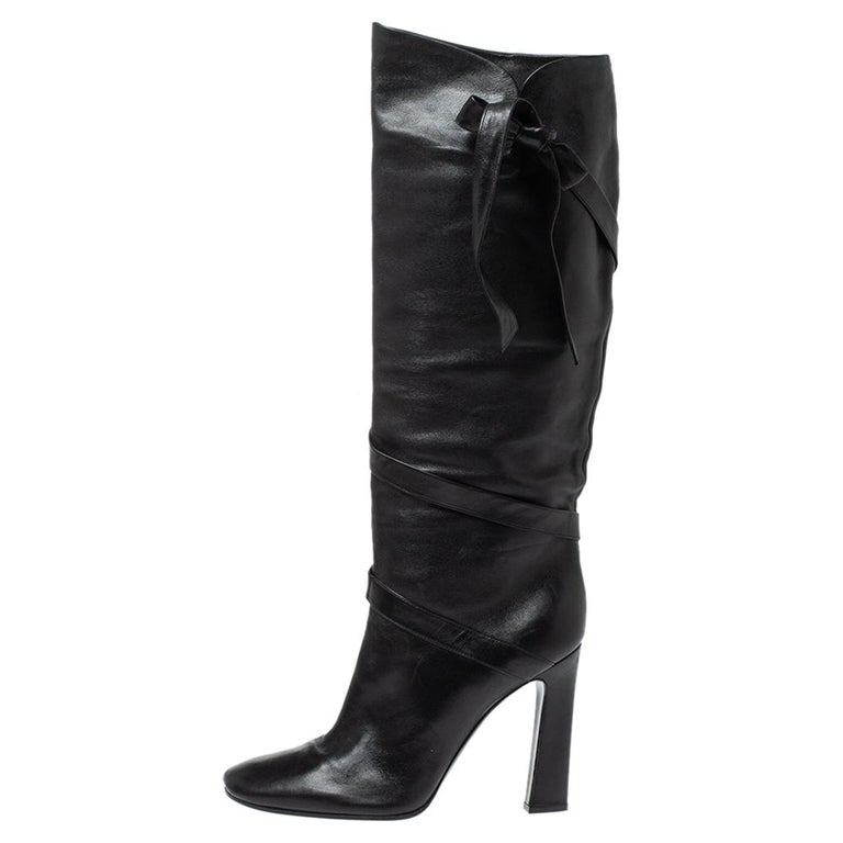 Casadei brings you this fabulous pair of knee-high boots that will give you confidence and loads of style. They've been crafted from leather in a classy black shade and styled in a sharp silhouette with a wrap detail that ends with a bow on the