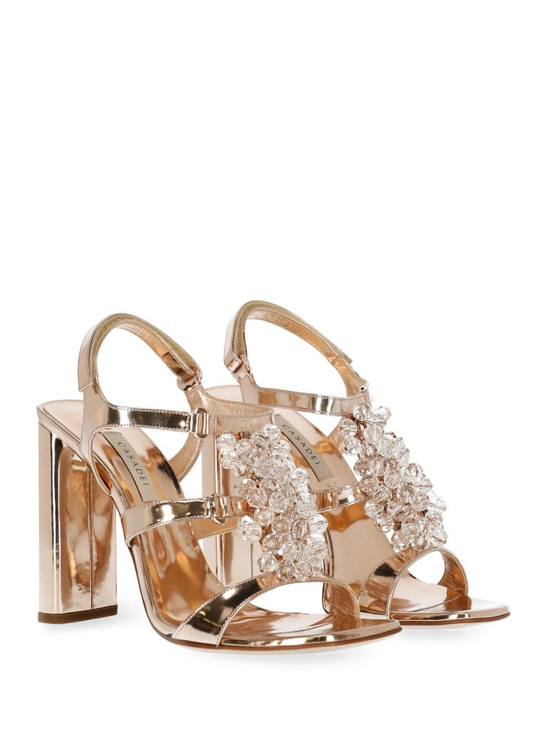 Shoe, leather, solid color, laminated effect, engraved logo, slingback strap, touch strap fastening, rose gold-tone hardware, branded insole, leather insole, high heel, crystal embellishment.  Includes: - Box - Dust bag  Product Condition: New With