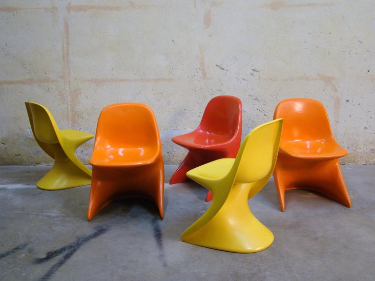 3 stackable plastic children seats, 2-orange and I-red. Very nice finish, strong colors, no fading with only few light scratches you might expect from use. An icon of children's seating by pop designer Alexander Begge, circa 1977.   The 2 yellow