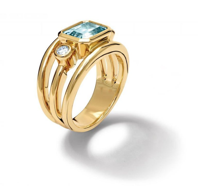Aeneus ring in 18ct yellow gold set with facetted emerald cut vibrant blue aquamarine and diamonds.