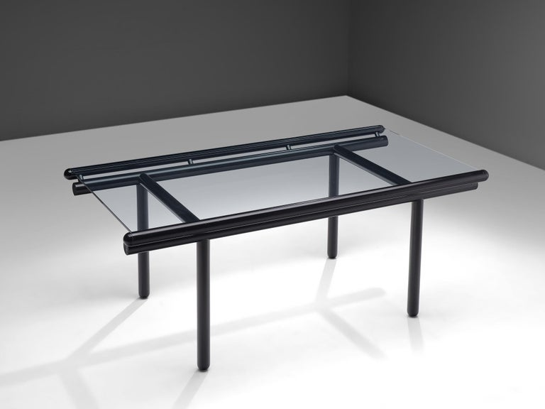 Cassina, 'Capri' dining table, glass and lacquered metal, Italy, 1970s.  The rectangular table has a clear glass top. The frame consist of four large tubular legs and double tubural lines that keep the glass top in its place, all executed in