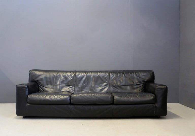 Three-seat sofa made entirely of black leather. The leather upholstery of the sofa is fully lined with its zippers.