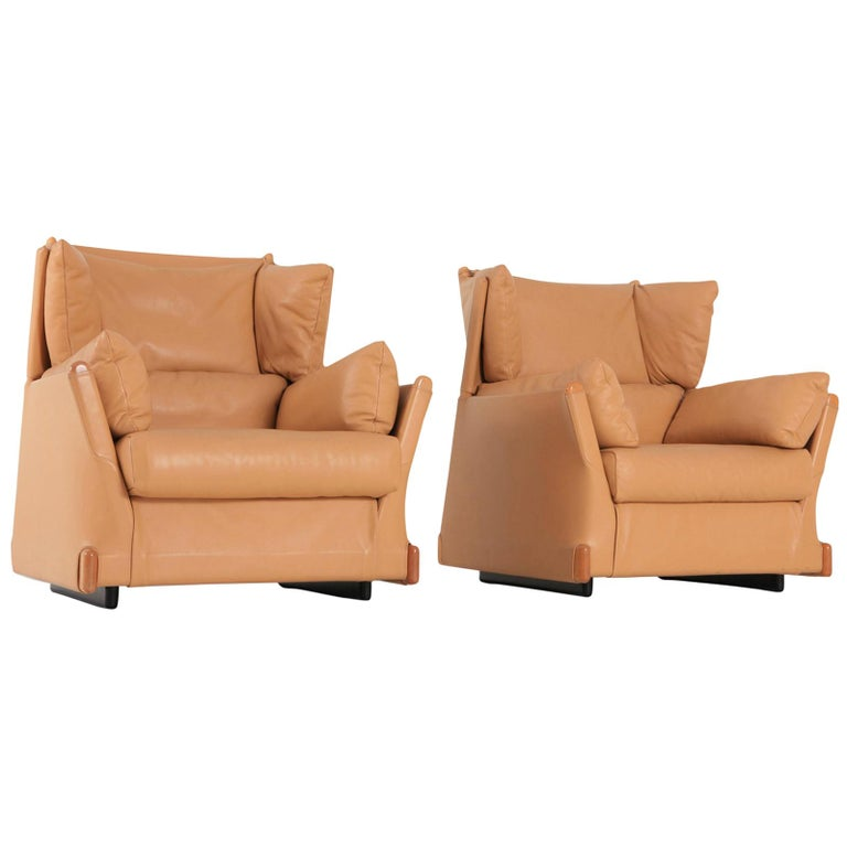 Postmodern luxury lounge chairs by Piero Martini for Cassina, 1970s. The camel leather and wooden details are in exceptionally well preserved condition.  Down filled cushions make these club chairs very comfortable too.