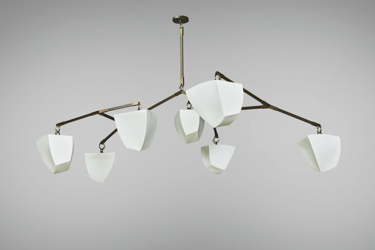 This is a horizontal mobile chandelier with 7 glowing cast porcelain polyhedrons. This fixture is also available with bamboo polyhedrons.  The Cassiopeia series was designed for spaces with lower ceiling heights where a horizontal chandelier is
