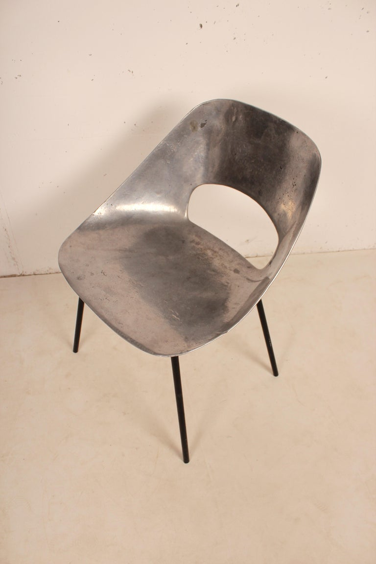 Stunning cast aluminum chairs by Pierre Guariche. Sculpted and curved aluminum seat with cut-out sits on sleek four leg black tubular metal base Great standalone piece.