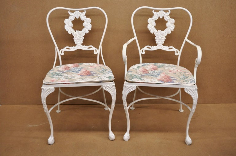 Cast Aluminum 7-piece Victorian style patio dining set table 6 chairs attributed to Molla. Listing features 5 side chairs, 1 armchair, glass top dining table, fruit harvest design backs, aluminum construction, and great style and form, circa late