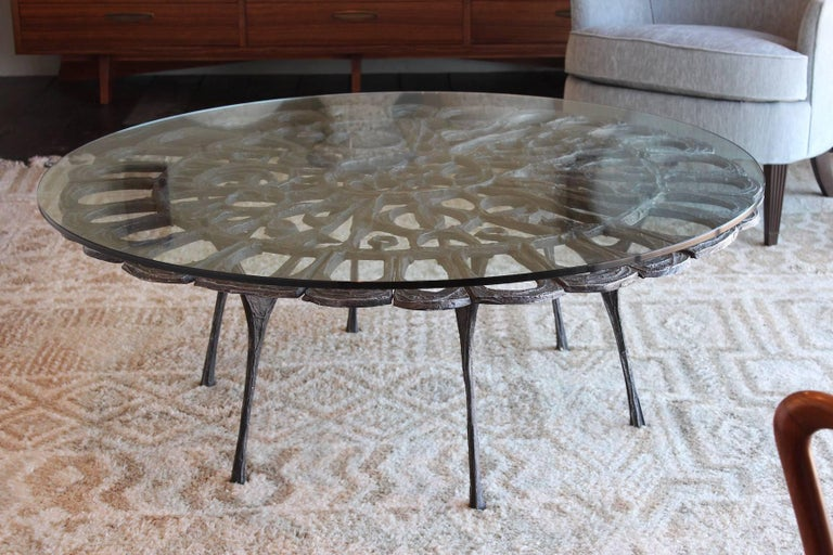 A sculptural cast aluminum coffee table with glass top. Designed by Donald Drumm.