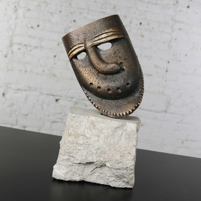Handsome cast bronze sculpture of African mask with a crooked nose. It is mounted permanently on a chunk of cut limestone with natural edge. It is in fabulous vintage condition, circa 1990s.