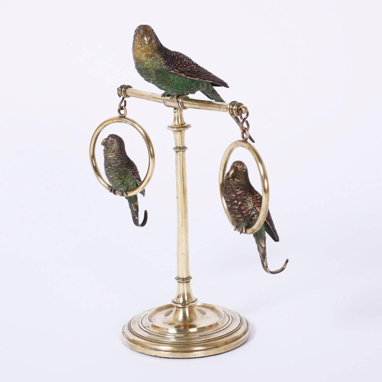 Three Vienna cast bronze and cold painted parakeets or birds perched on a brass Stand with a Classic turned base, in the manner of Franz Bergman.