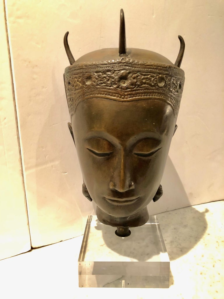 """Striking cast bronze Thai head of a deity. The top of the head is open to allow for the burning of incense. The piece is mounted on a custom Lucite riser that measures 6"""" square the piece has beautiful detail and patina."""