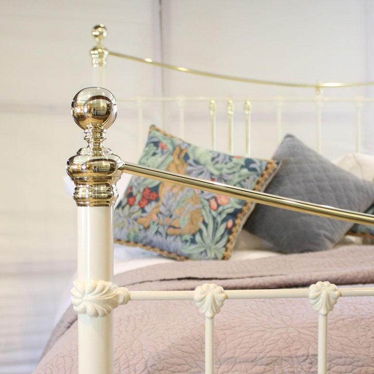 Cast iron and brass bed finished in cream with curved brass top rails and decorative cast iron mouldings. Adapted to the 6'0 width from an original Victorian frame.   The price includes a standard firm bed base to support the mattress.   The