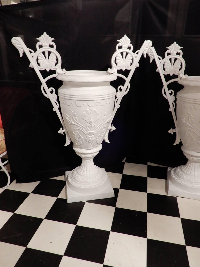 A pair of elaborate 19th century urns in the Renaissance Revival style, often referred to as the Egyptian style in the 19th Century. These urns are by the Mott Foundry of NY, who was the chief competitor of Fiske. Several years ago another urn with