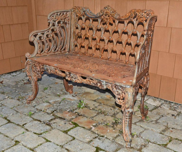 This Gothic pattern style cast iron bench is weathered with great patina. Garden seat is pierced and with cabriole legs. The style is known as the White House Rose Garden bench because the style was seen in the White House. This seat was originally