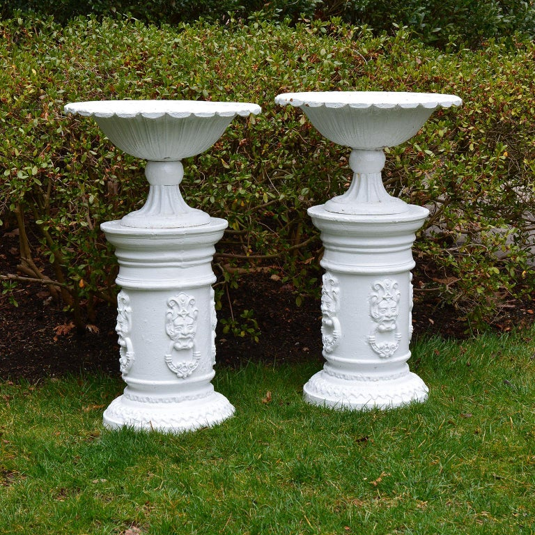 A fine pair of cast iron tazza form urns with fluted foot and scalloped rim, English, circa 1930, on associated pair of cast iron pedestal columns with masks. Measures: Overall height 36.5 ins. The urns 13 ins. high, 22 ins. overall diameter, the