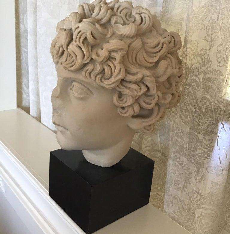 Cast marble bust of a Roman child set on a base size: 3.50 H x 5.25 W x 6 D.