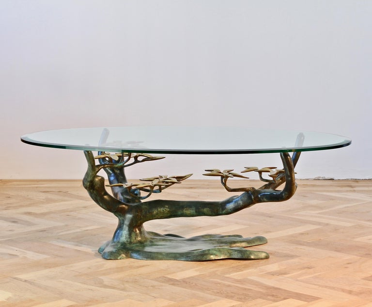 Whimsical vintage Willy Daro inspired coffee / cocktail table, cast in brass, takes on the organic form of a 'Bonsai' tree with the very stylized flower petals, while the patinated green branches hold a thick beveled edged clear glass table top. The