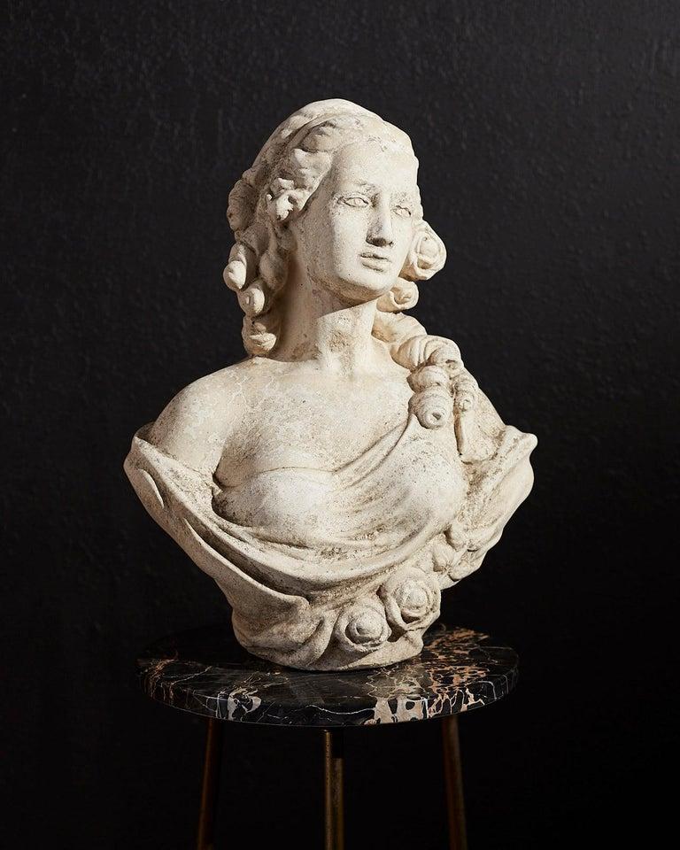 Beautiful cast stone garden bust sculpture of French Queen Marie Antoinette (1755-1793). Very heavy and solid with a lovely distressed patina of an aged marble piece. Depicted with curly locks of hair, roses on her dress and a mesmerizing gaze.