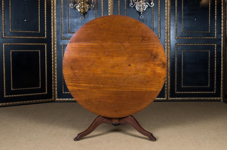 Massive mahogany. Round column shaft, below which are three volute-shaped curved legs. Straight cheeks for round tabletop. The table is equipped with a folding mechanism.  On the reverse stamped K.P for the palace Royal Palace.  Similar table in the