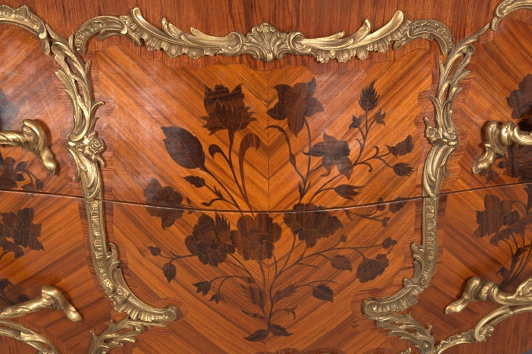 Rosewood and shaded precious wood, veneered. In the front two drawers, in the front and on the side walls broadly framed fillings with richly inlaid blooms of different noble wood, limited by so-called mirror veneer. On the corresponding sides and