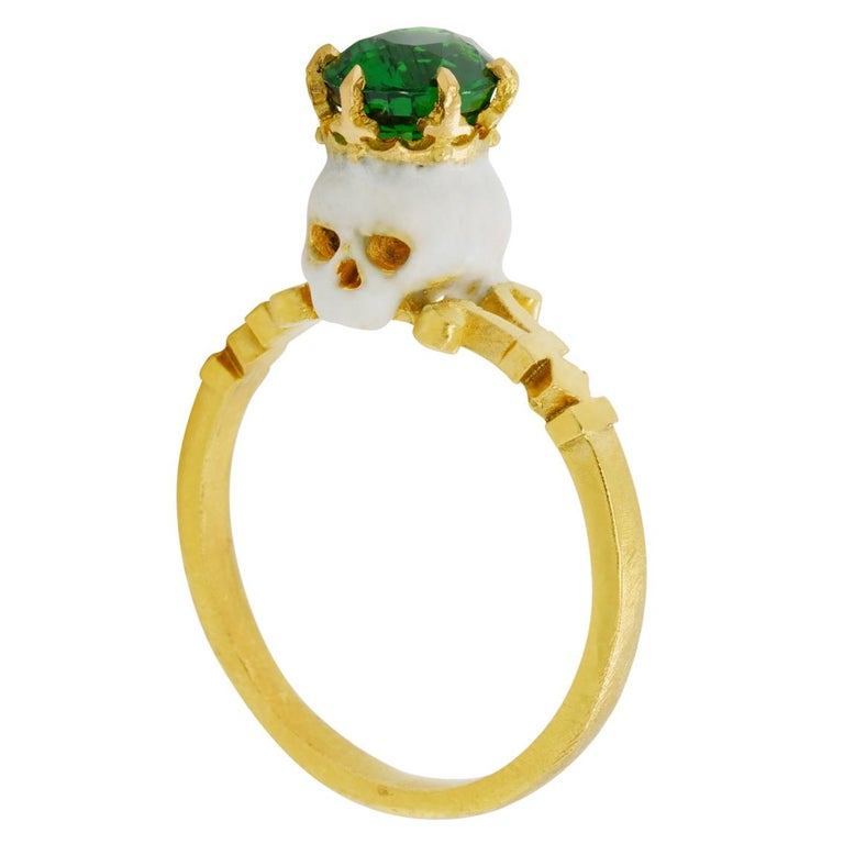 Handcrafted in luxurious 22kt yellow gold this stunning ring features a saintly baroque style enamelled skull adorned with a crown and hypnotic 7.4mm x 6.2mm 1.6ct Tsavorite garnet perched atop a signature William Llewellyn Griffiths split shank.