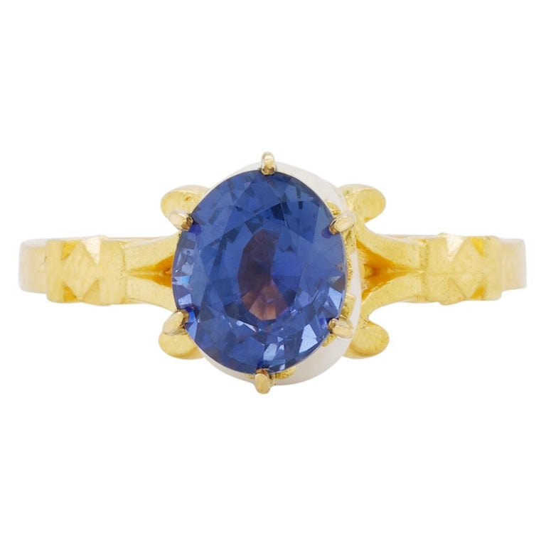 Handcrafted in luxurious 22kt yellow gold this stunning ring features a saintly baroque style enamelled skull adorned with a crown and exquisite 7.63mm x 6.52mm x 4.51mm 1.8 carat sapphire with color shift from violet to shades of blue and purple