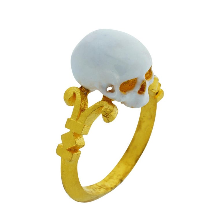 Handcrafted in luxurious 24kt yellow gold this stunning ring features a saintly baroque style enamelled skull perched atop a signature scrolled William Llewellyn Griffiths split shank.   Measuring 9mm above the finger this sumptuous memento mori