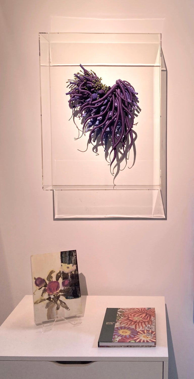 Framed in a clear acrylic shadowbox, Catherine Latson's Specimen 24 reads as an artistic rendition of a beautiful sea specimen. Rich, jewel-toned purple hand-dyed cotton thread is wrapped around tendrils that stretch from a delicate cluster of tiny