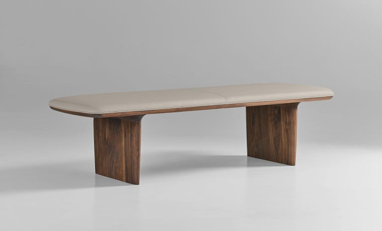Elemental bench with solid walnut frame and upholstered seat. Available in various standard fabric and leather options as well as COM and COL. Standard with centre seam and welt around seat. For seamless seat specify railroaded. Leather will have