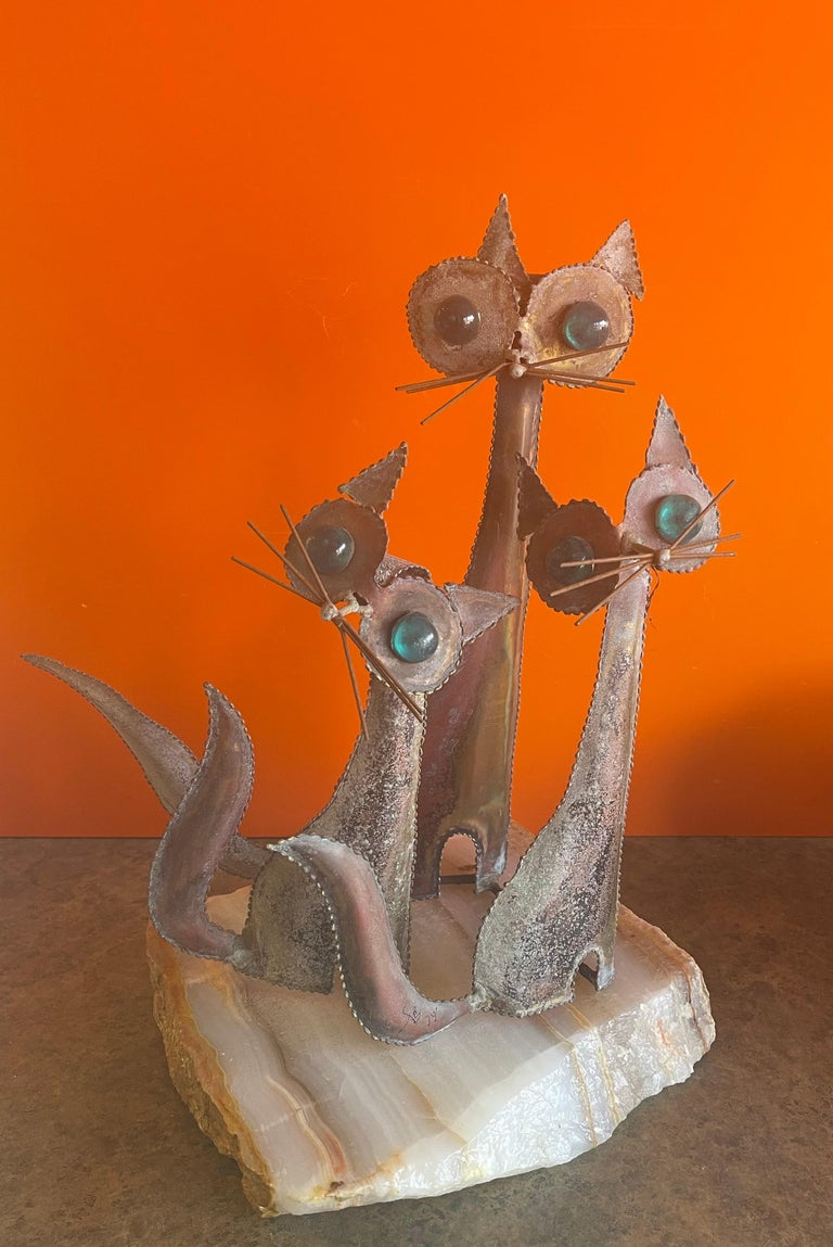 A very cool and rare cats sculpture on a solid block of white onyx in the style of C. Jere, circa 1974. The piece is signed and dated and has a wonderful patina. The cats eyes are a bright teal color that blends beautifully with he aged patina of