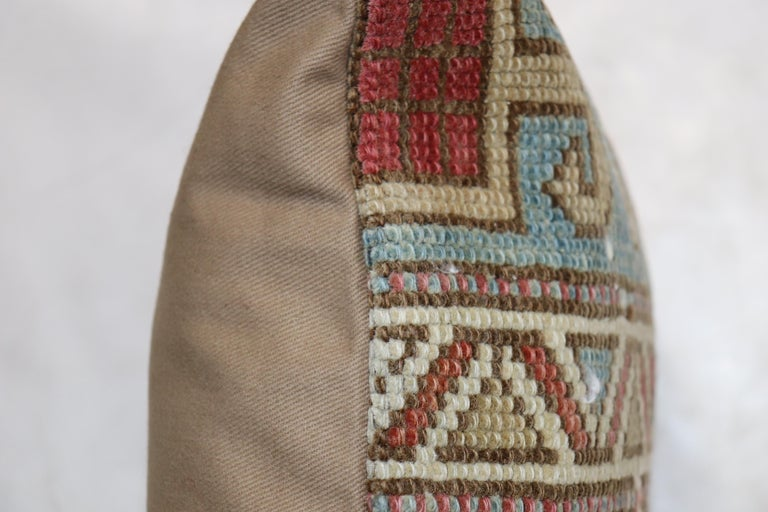 Pillow made from an early 20th century Caucasus rug in a soft warm palette in rustic colors. zipper closure and poly-fill insert provided.  Measures: 14