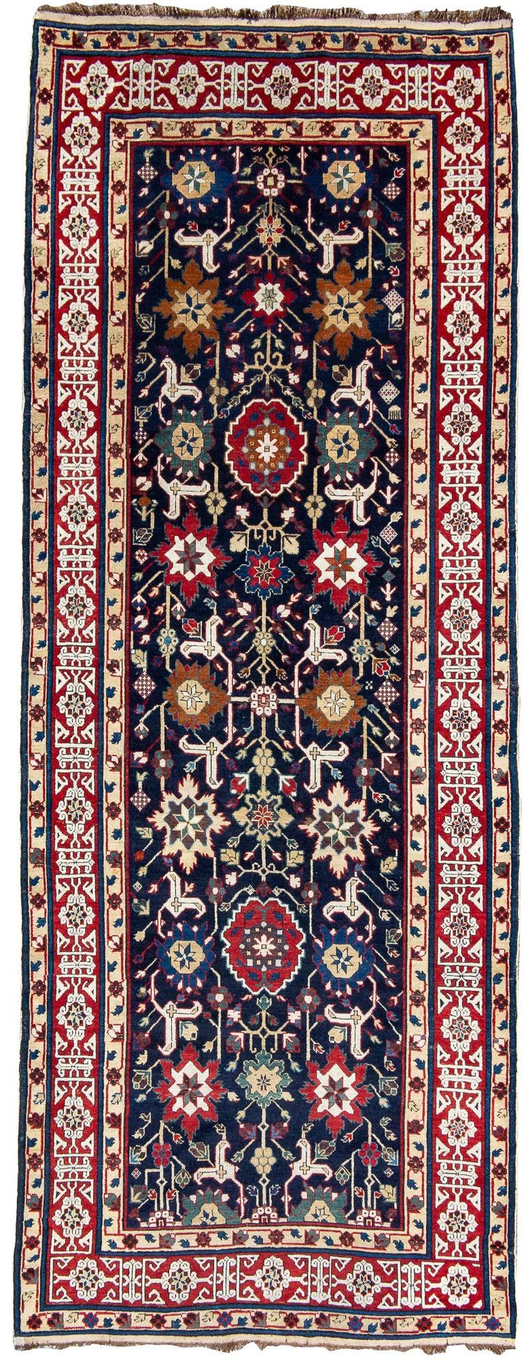 Woven in the east Caucasus near the Caspian coast, this Shirvan long rug uses perfect scale of drawing accentuated by vibrant saturated color. The field is composed of abstract floral ornament with a central column of varying rosettes flanked on