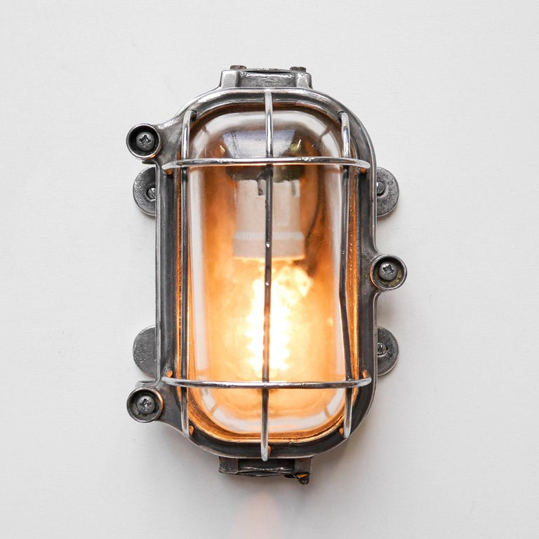 Old industrial wall light, from us. In die- cast aluminium, picked and polished, curved fence protecting a thick transparent glass. Put it horizontally or vertically!