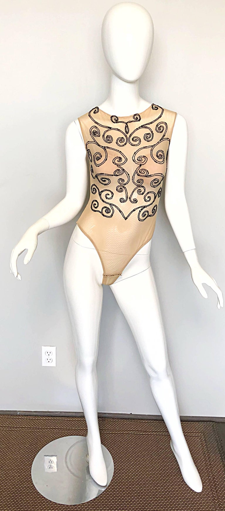 Sexy 1990s C.D GREENE Couture nude and black beaded sheer bodysuit! Features a double layered nude mesh with thousands of hand-sewn black seed beads throughout the front. Hidden zipper up the back with hook-and-eye closure. Built-in nude cups to
