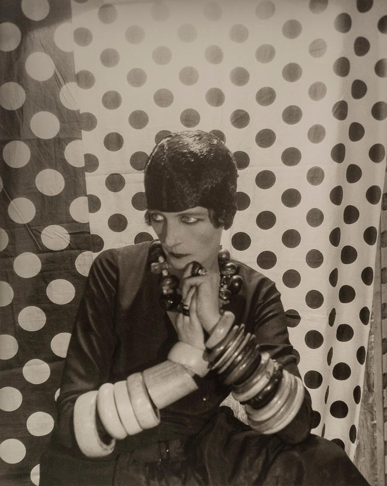 Nancy Cunard, 1929 - Cecil Beaton (Portrait Photography) Signed on mount Stamped with photographer's studio ink stamp on reverse of mount Silver gelatin print mounted on card, printed 1970s 22 x 17 inches  Cecil Beaton (1904-1980) had a brilliant