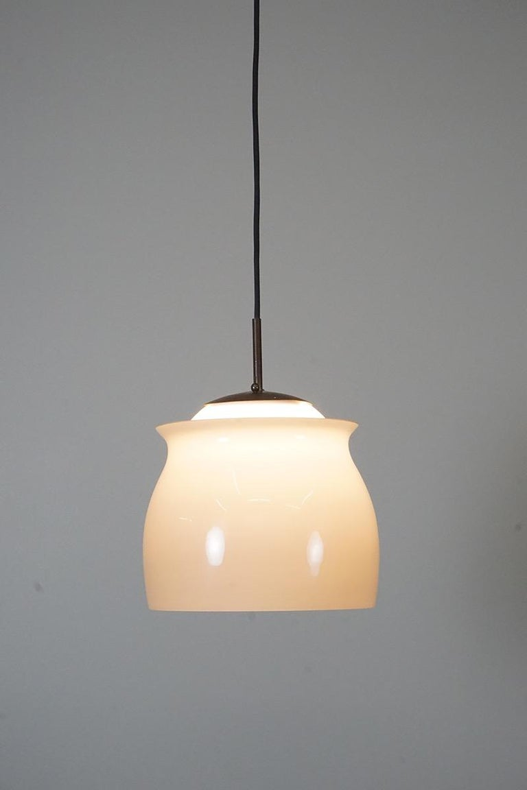 Pendant made of hand blown opal and flashed glass in warm gray. Metal mounting.