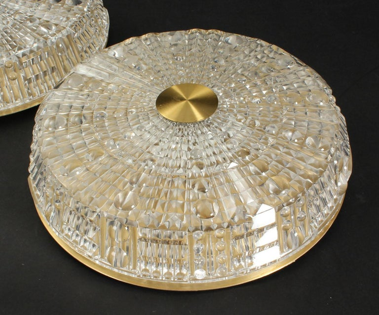 Carl Fagerlund for Orrefors. Ceiling lamps with screen of pressed clear glass, back plate and top of brass. Manufactured by Lyfa. 1960s-1970s. Ø 40 cm. Sold separately.