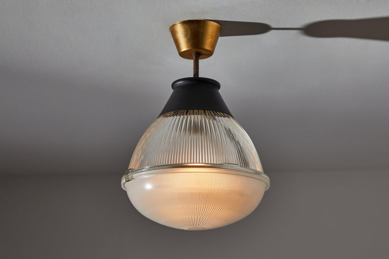 Ceiling light by Tito Agnoli for Oluce. Designed and manufactured in Italy, 1958. Holophane glass diffuser, original brass canopy. Wired for US standards. We recommend one E27 100w maximum bulbs. Bulbs provided as a one time courtesy.