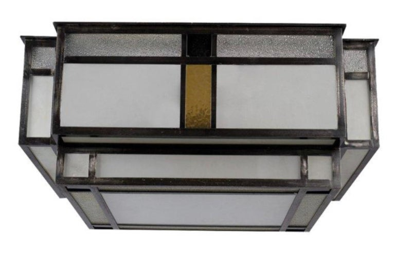 Modernist ceiling light in a two-level square shape, patinated metal structure encircling cut glass, satin, granite and coloured plates. A pair is available.