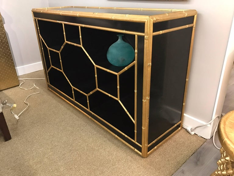 Great looking chinoiserie style black credenza with all open storage and trimmed in a gold gilt faux bamboo.  Designed by Celerie Kemble for Henredon.
