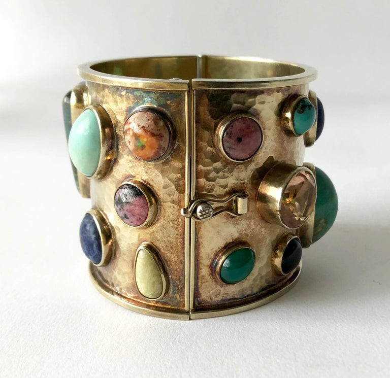 Multi colored semi-precious gemstones set in a sterling silver hinged cuff, created by Celia Harms of Mexico.  Each stone is bezel set within a hand hammered silver, gold washed bracelet.  Bracelet has a wearable wrist length of 6.75