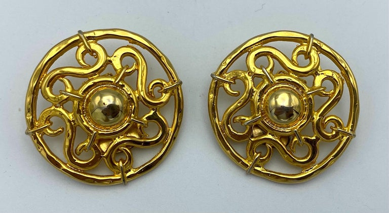 An elegant pair of large Celine openwork design earrings from the 1990s. The earrings are beautifully cast and gold plated with a central dome surrounded by scrollwork within a round frame. Each earring measures 1.5 inches in diameter and .25 of an