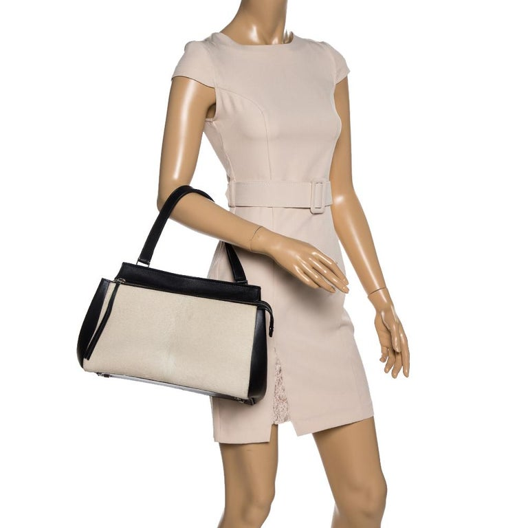 This Céline Edge bag is not only visually magnificent but also functional. It has been crafted from beige calfhair and black leather and styled with a silhouette that is classy and posh. The bag has a top handle and a front zipper that reveals a