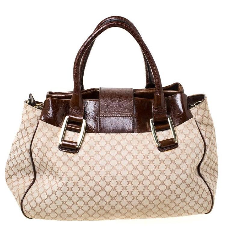 This beige/brown satchel from Céline is sure to grab a special place in your closet. Crafted from Monogram canvas and enhanced with leather trims it features striking details such as the engraved metallic gold lock closure at the front, dual